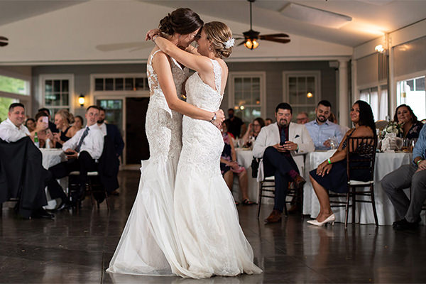 Two brides dancing their first dance together at a wedding reception