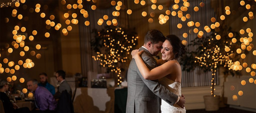 a bride and groom dancing the first dance at their wedding reception. There are lots of twinkle lights behind them.