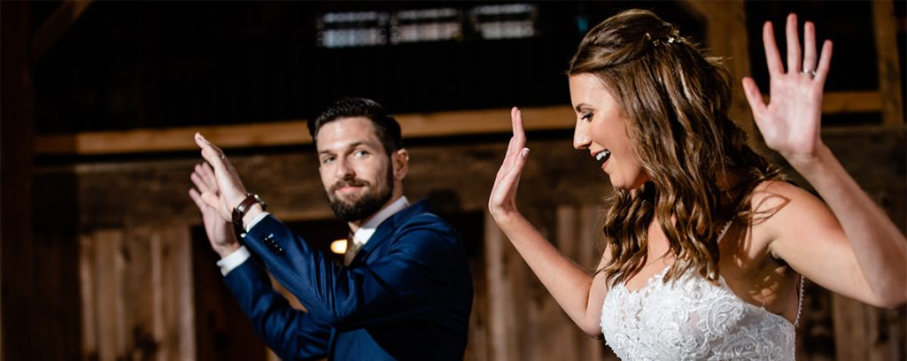 A bride and groom doing a fun dance at their wedding. It is their first dance and they are dancing to their favorite songs.