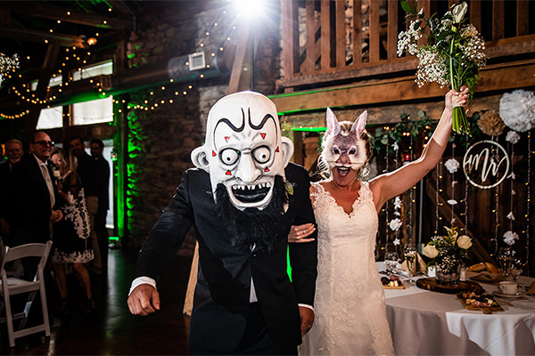 a bride and groom walking into wedding reception wearing rock and roll masks