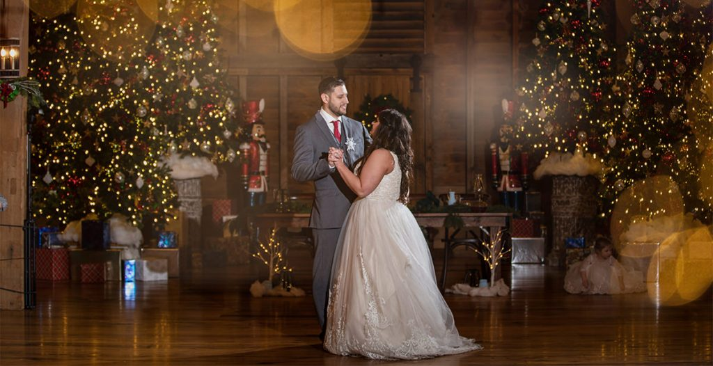 A bride and groom doing a first dance at their wedding reception. There are Christmas trees and lights behind them.