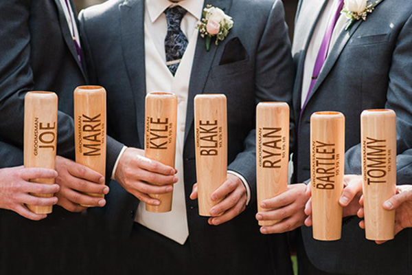 a photo of groomsmen holding baseball bat mugs that were given to them as a gift from the groom.