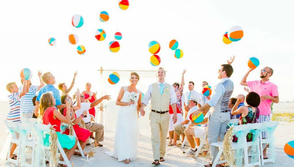 a bride and groom exiting their beach wedding ceremony as the guests throw beach balls