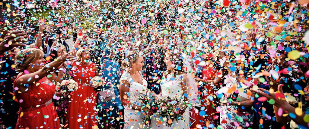 Two brides celebrating being married as their guests shower them with biodegradable confetti