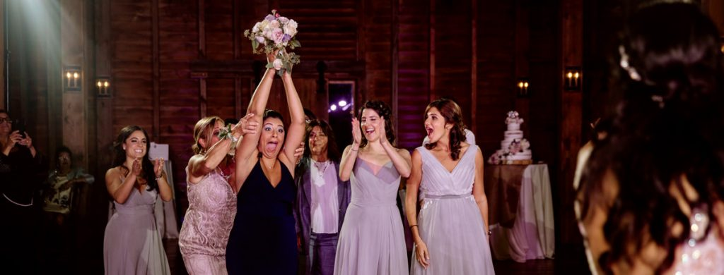 A group of girls trying to catch the bouquet after the bride tossed it