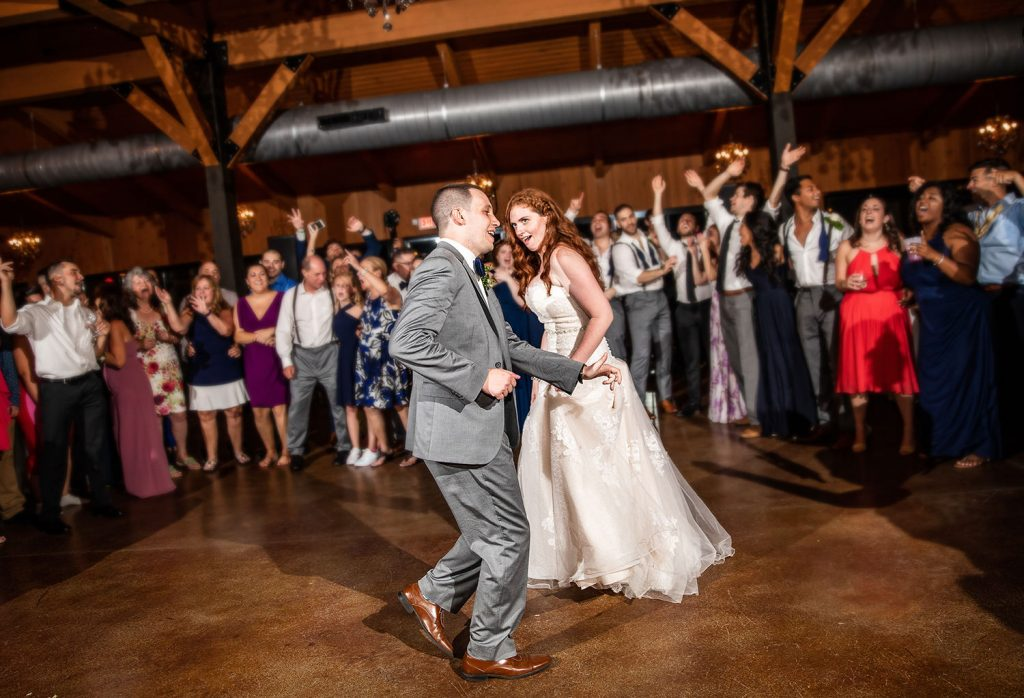 a photo of a brother dancing with his sister at a wedding. They are dancing to the best songs.