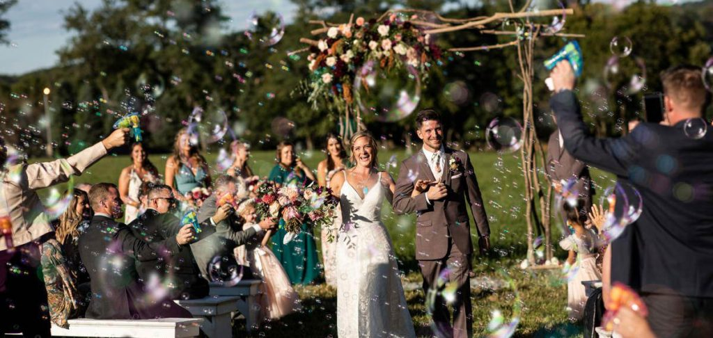 A bride and groom walking down the aisle after their wedding ceremony as guests blow bubbles