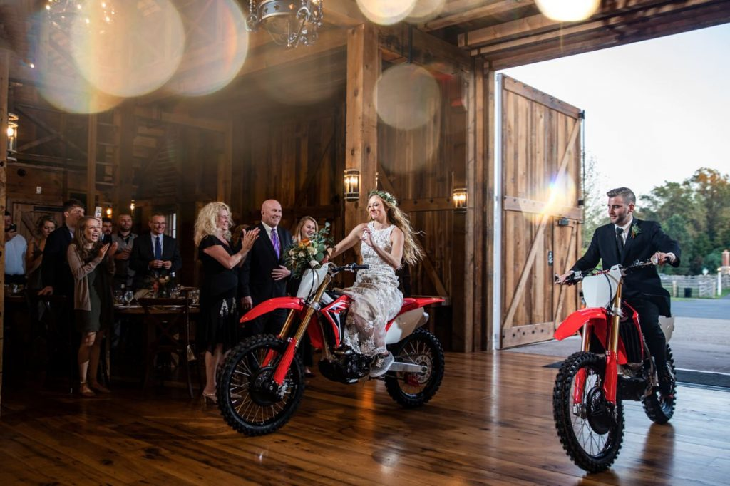 A bride and groom arriving to the wedding reception on Honda dirt bikes
