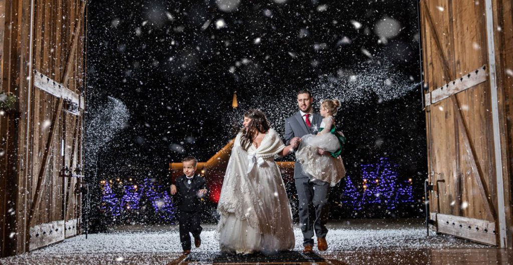 A bride and groom doing a wedding reception exit or entrance with fake snow