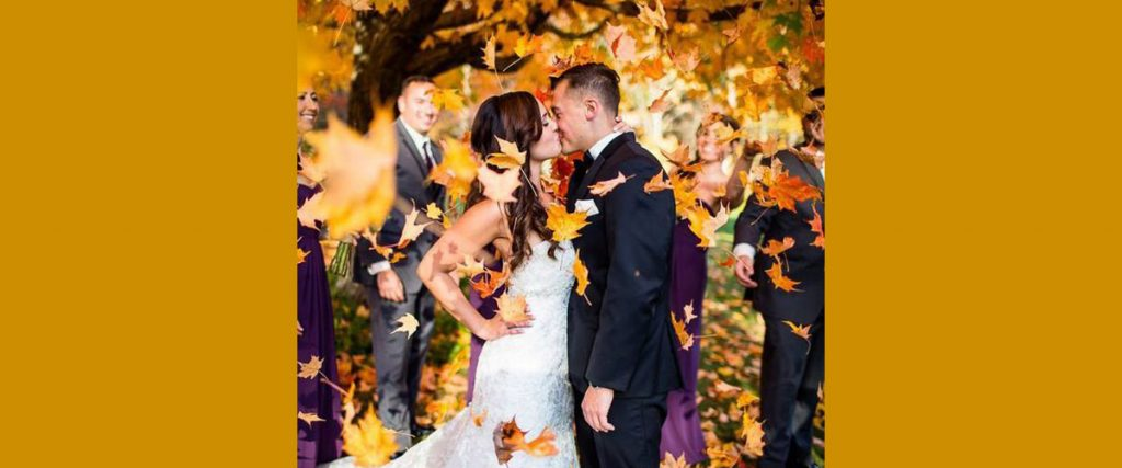 a bride and groom kissing under fall colored trees