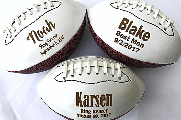 3 footballs that are personalized from the groom to the ring bearers at a wedding