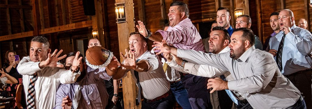 A bunch og guys diving to catch the garter that was tossed by the groom. The DJ was playing a funny garter removal and toss songs
