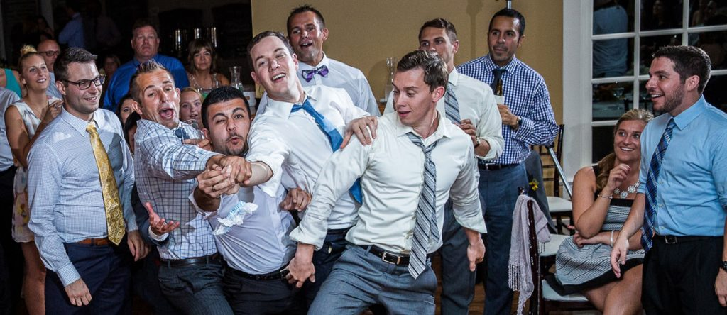 A group of guys trying to catch the garter after the groom tossed it at the wedding reception.