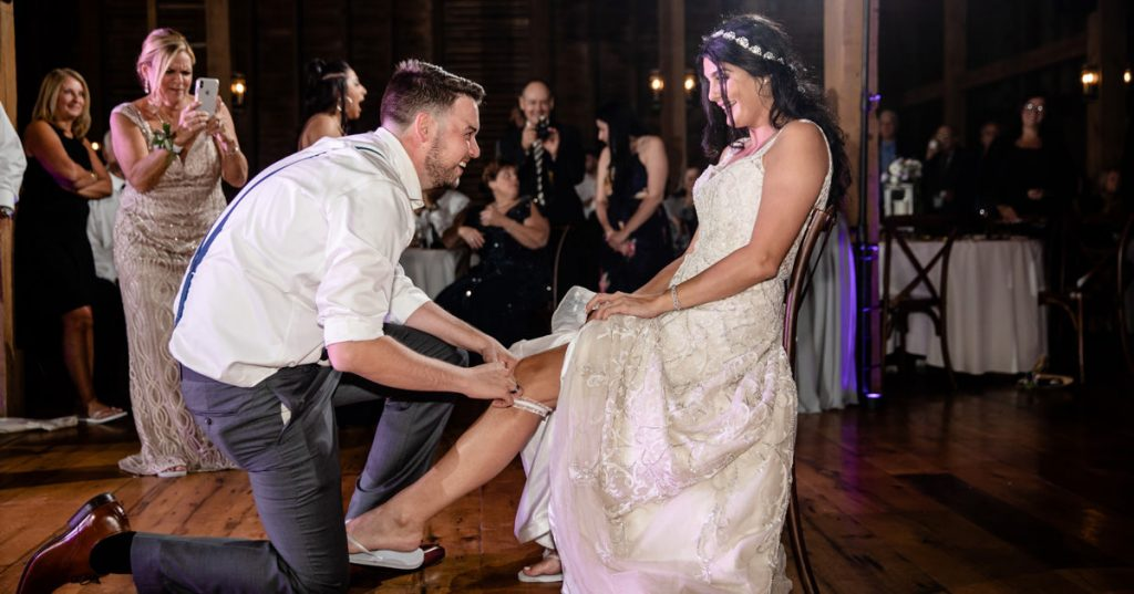 A groom removing the garter from the bride's leg during the wedding reception.