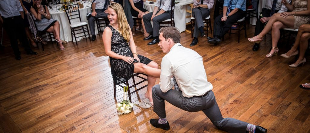 The wedding guest who caught the garter is now putting it on the leg of the girl who caught the bridal bouquet