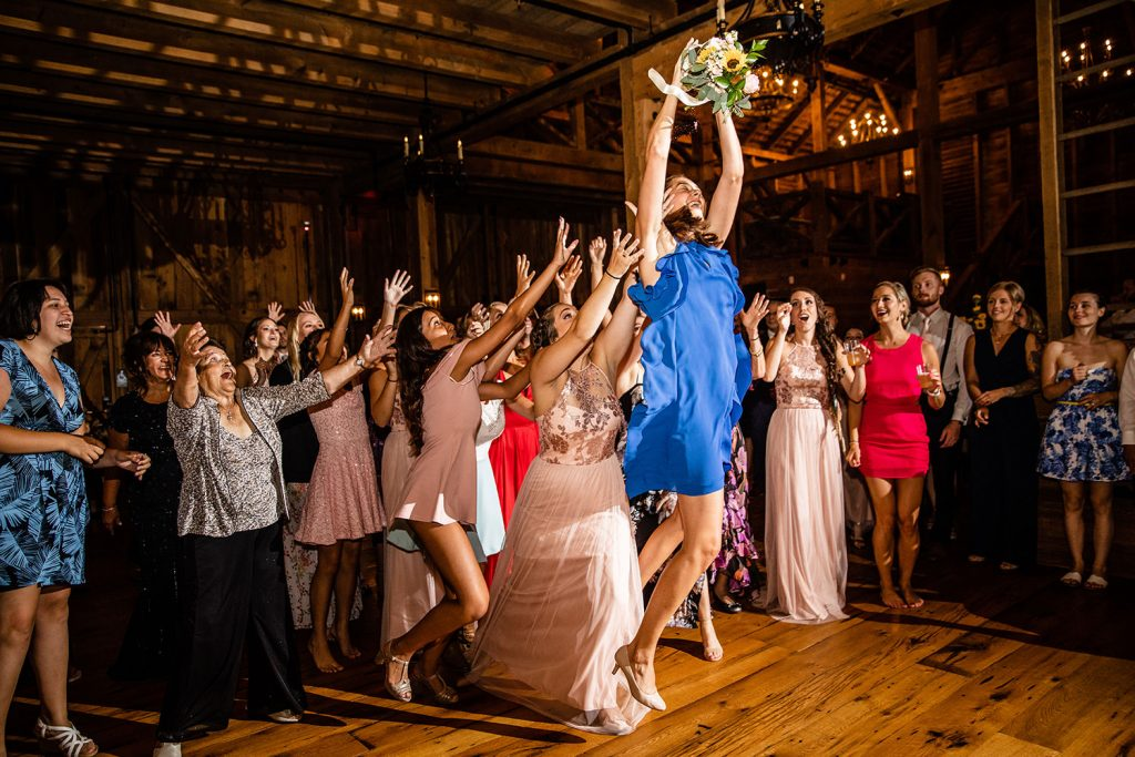 A wedding guest jumping high in the air to catch the bridal bouquet after the bride tossed it