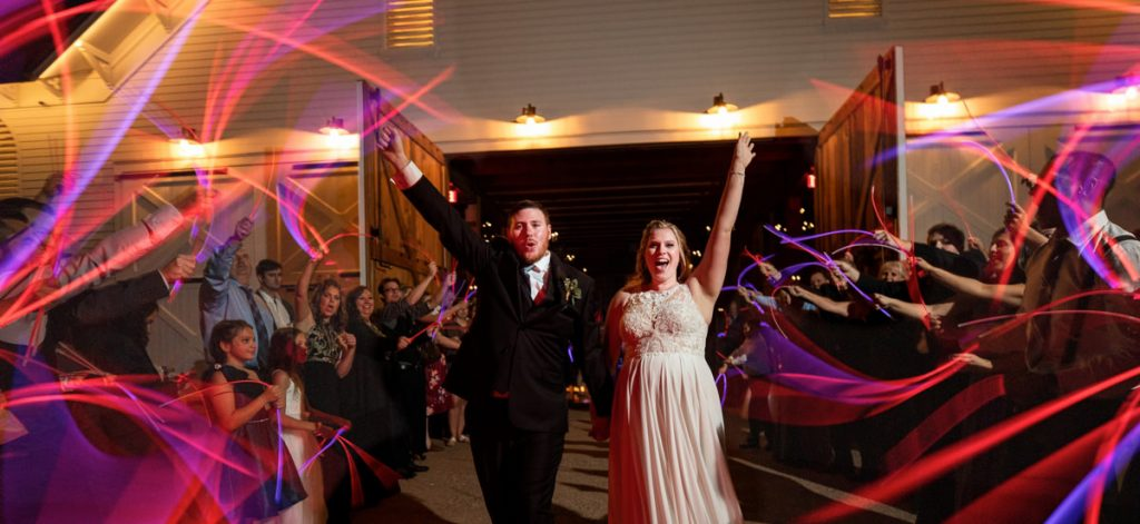 A bride and groom doing a wedding reception exit with glow sticks