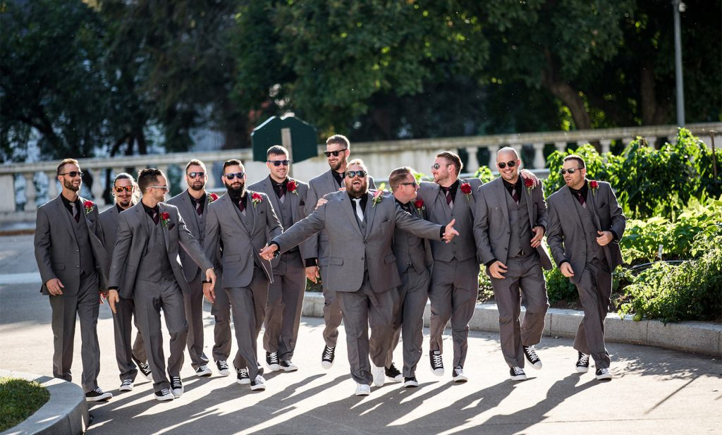a groom and groomsmen walking down the street