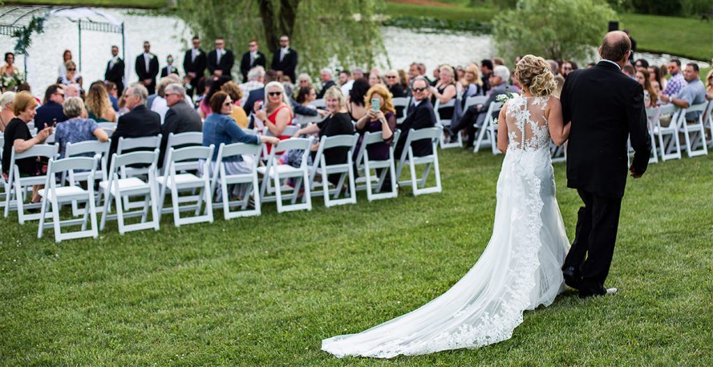 A bride walking down the aisle to a modern instrumental song on her wedding day. The photo is taken from the back of the aisle.