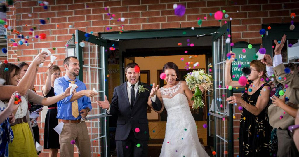 A bride and groom walking out of their wedding ceremony as guests throw pom pom balls at them