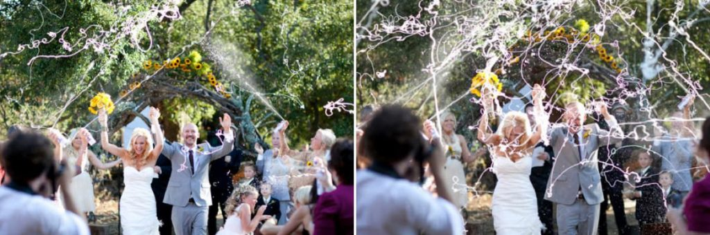 A bride and groom walking down the aisle for the ceremony exit and guests are spraying silly string on them