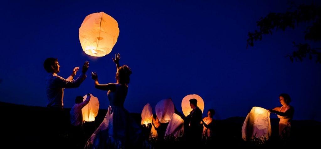 A wedding couple doing a sky lantern send off after their wedding reception