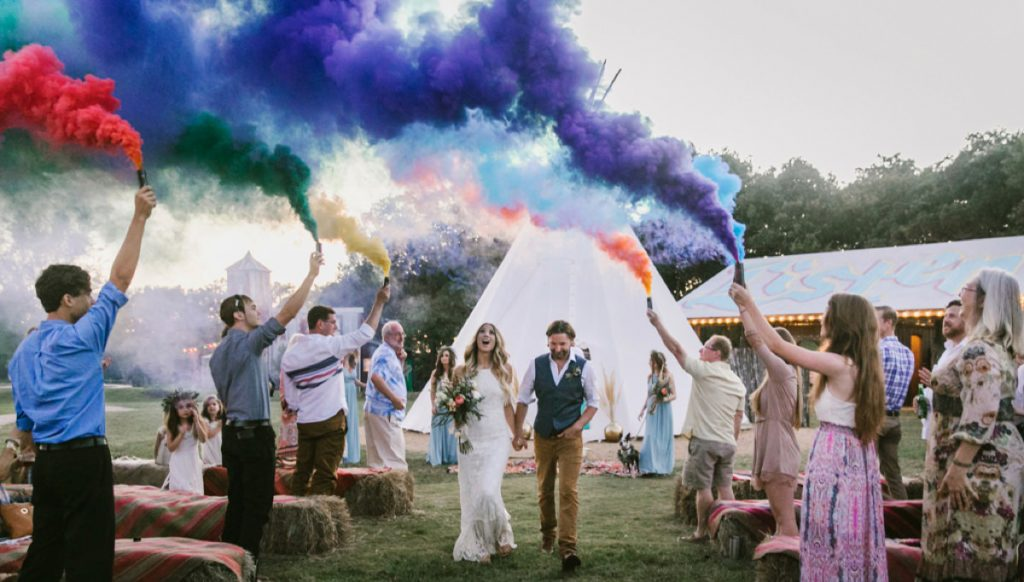 A bride and groom using smoke bombs for the wedding ceremony exit