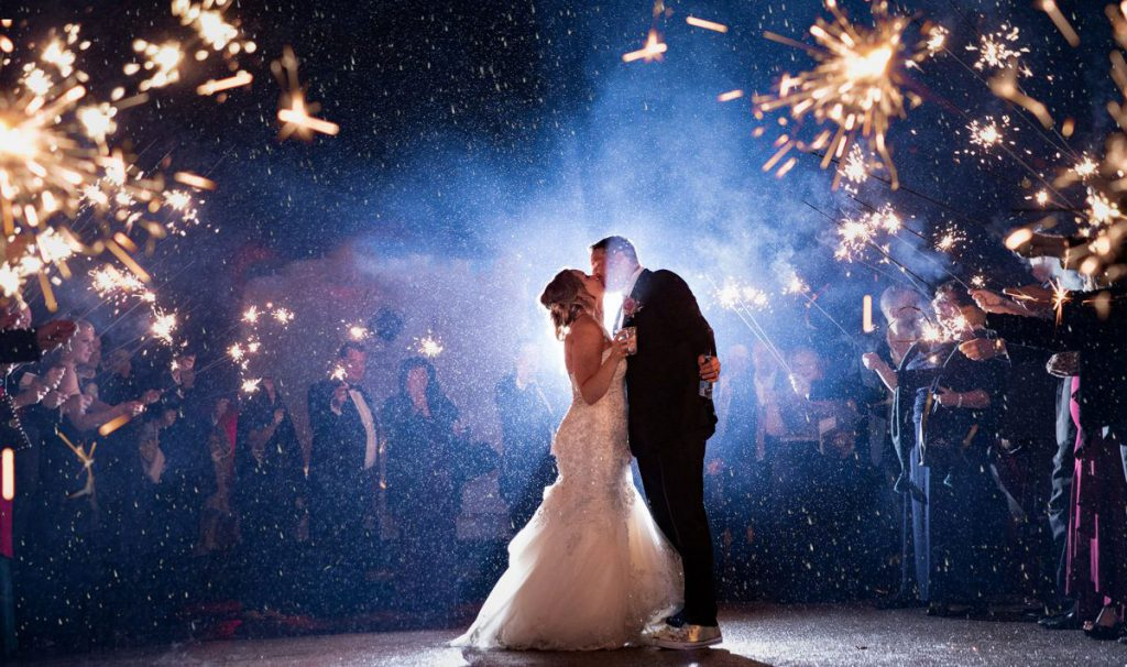 A bride and groom standing in the rain while doing a sparkler exit after the wedding reception.