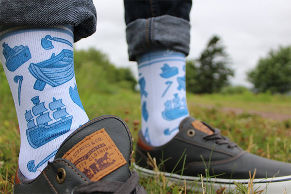 A close up of a guy wearing socks that have a photo of boats and hoes on them.