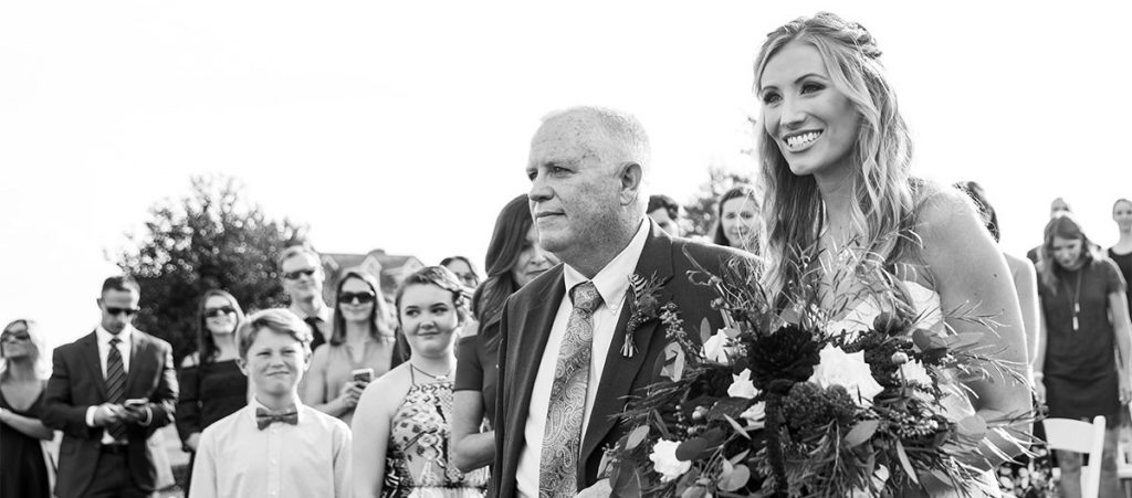 A bride and her father walking down the aisle at the wedding ceremony processional