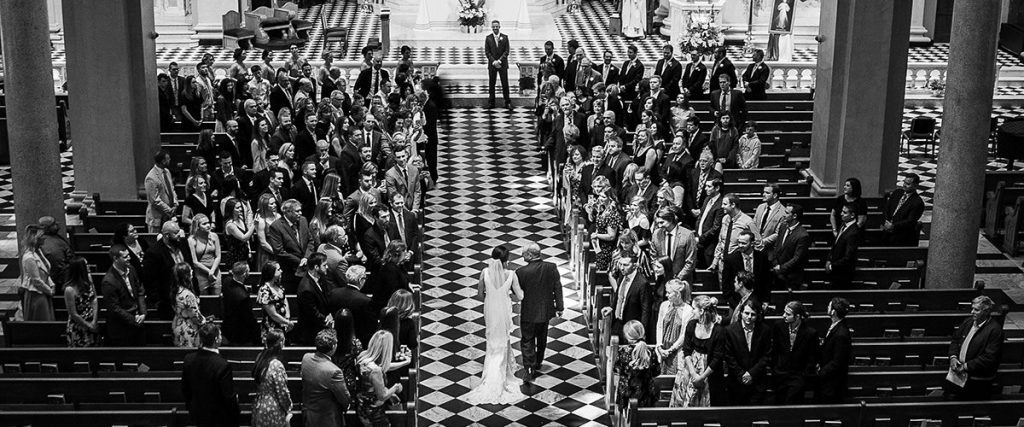 The bridal wedding ceremony processional to a great song. This photo is taken from above of the bride and her father walking down the aisle.