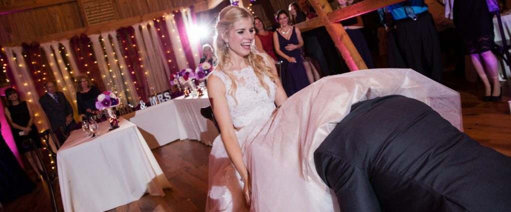 A groom removing the garter from the brides leg. The DJ is playing a funny song as he removes it.