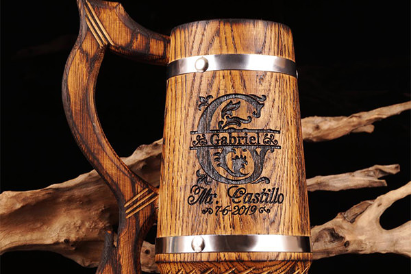 Wooden beer stein sitting on a table. This one has engraving on the side because it was a gift from the groom to his groomsmen