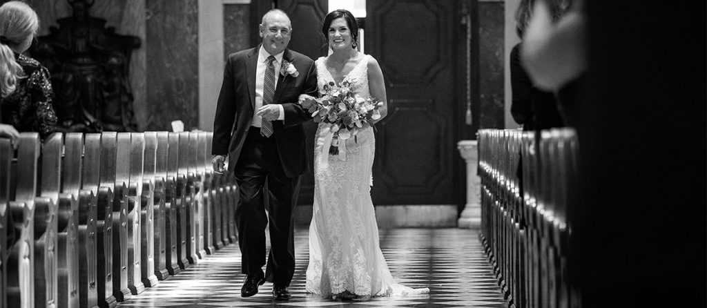 A bride and her dad walking down the aisle at the wedding ceremony