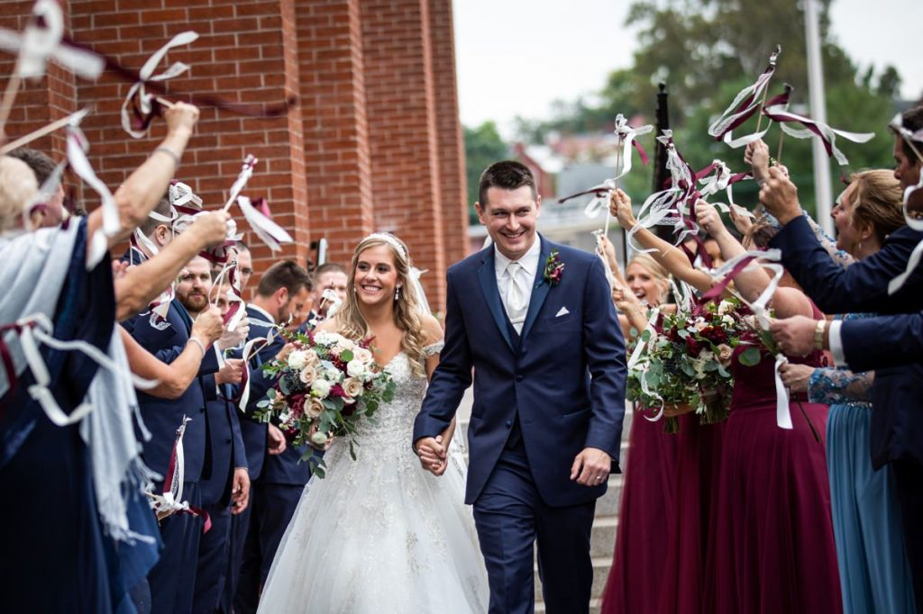 A bride and groom leaving their ceremony as guests wave ribbon wands and streamers