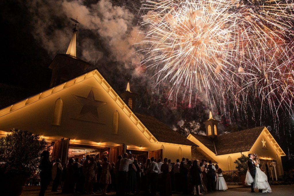 A bride and groom kissing while fireworks go off at their wedding reception exit
