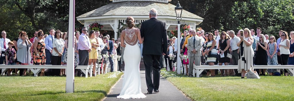 A photo taken from the back of the bride walking into the ceremony to an amazing song. This part of the wedding is called the processional