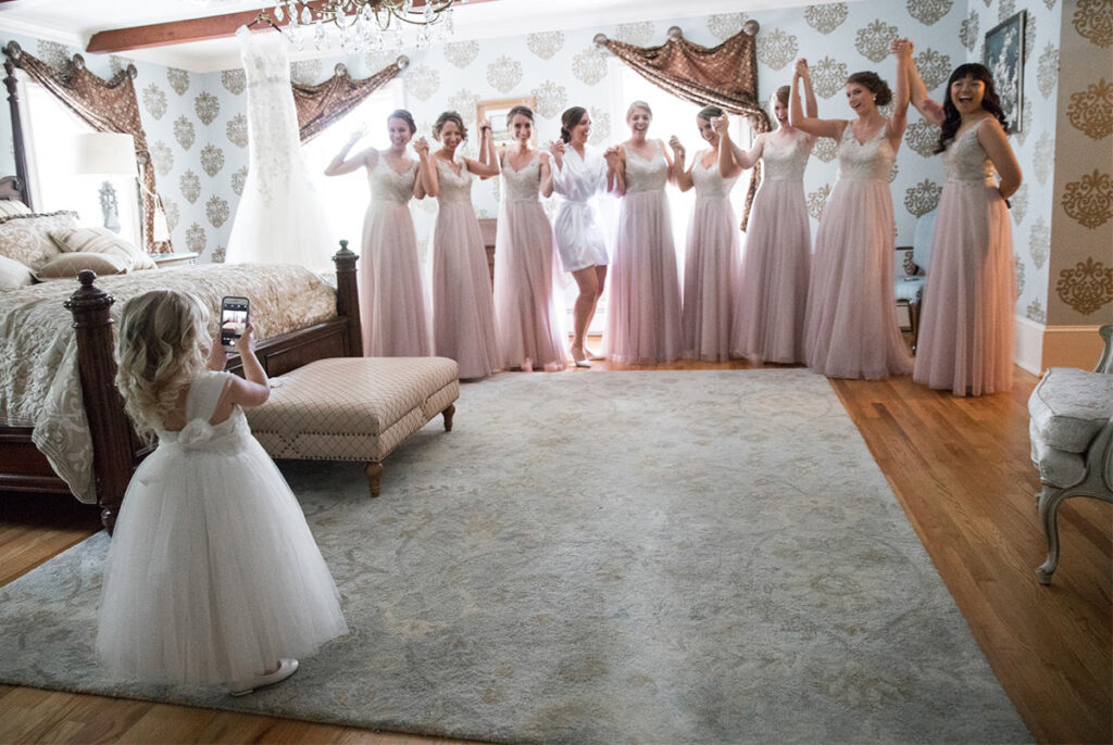 A cute flower girl taking photos of the bride and bridal party. This is the top cover photo for the best wedding photographers in Philadelphia article