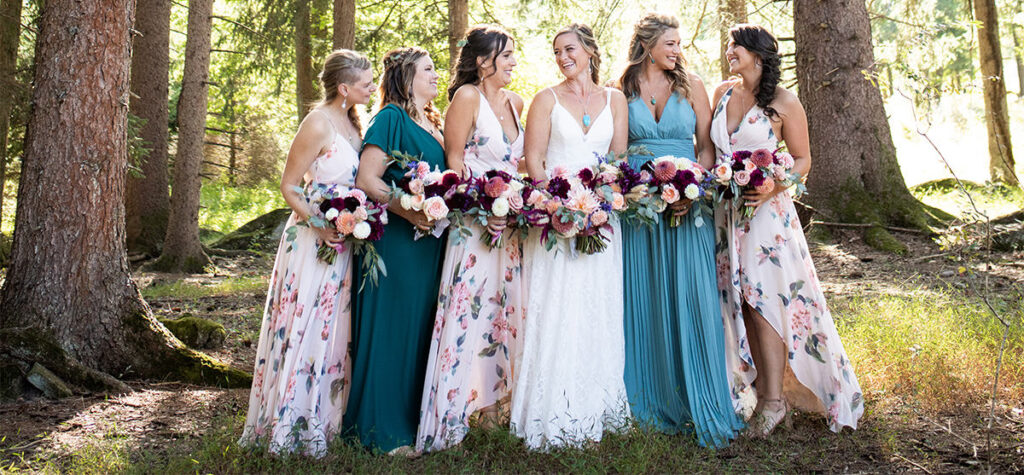 Bridesmaids posing in the trees looking at each other
