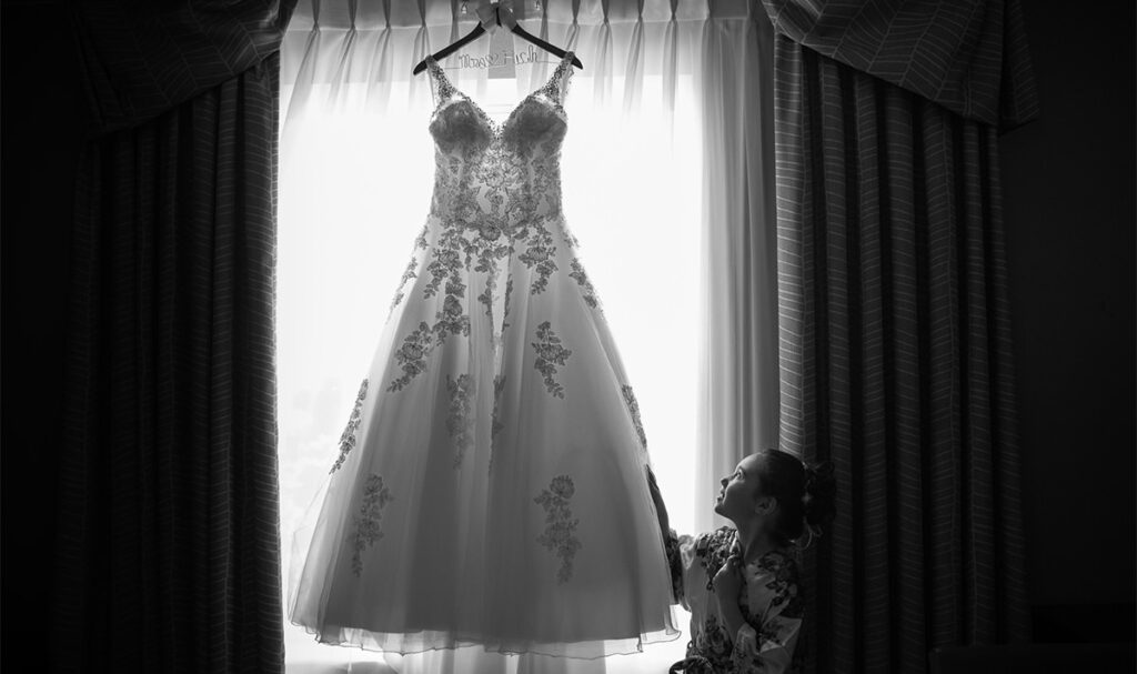 A flower girl looking at the wedding dress hanging in the window.