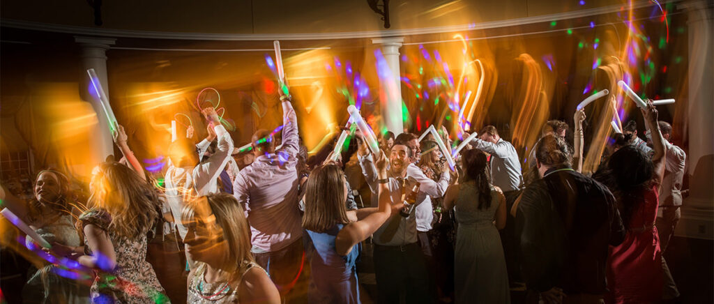 Wedding guests dancing at the reception with glow sticks.