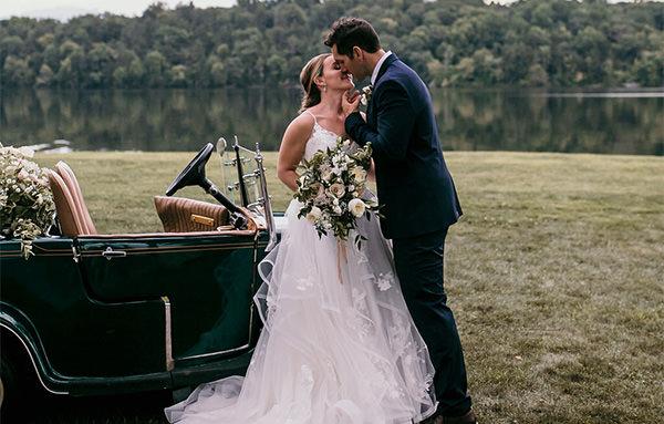 A bride and groom kissing near a car