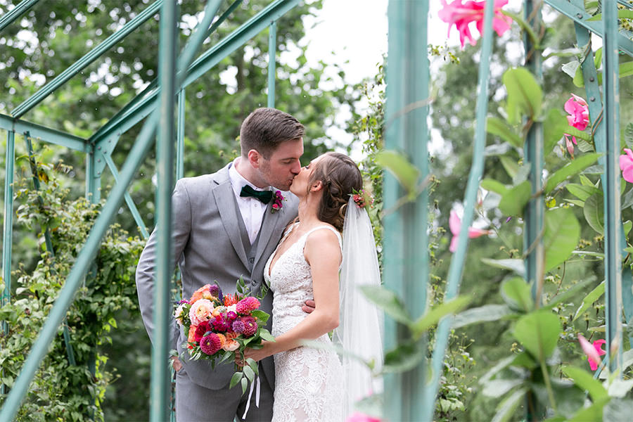 A bride and groom kissing in a greenhouse