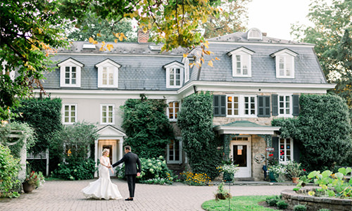 A bride and groom dancing in front of a mansion. This is one of the cover photos for the article best wedding photographers in Philadelphia, PA