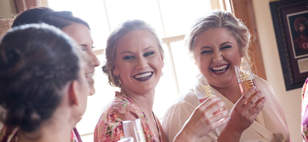 A bride having a champagne toast with her bridesmaids. This is on of the photos that should be included in your wedding photography shot list.