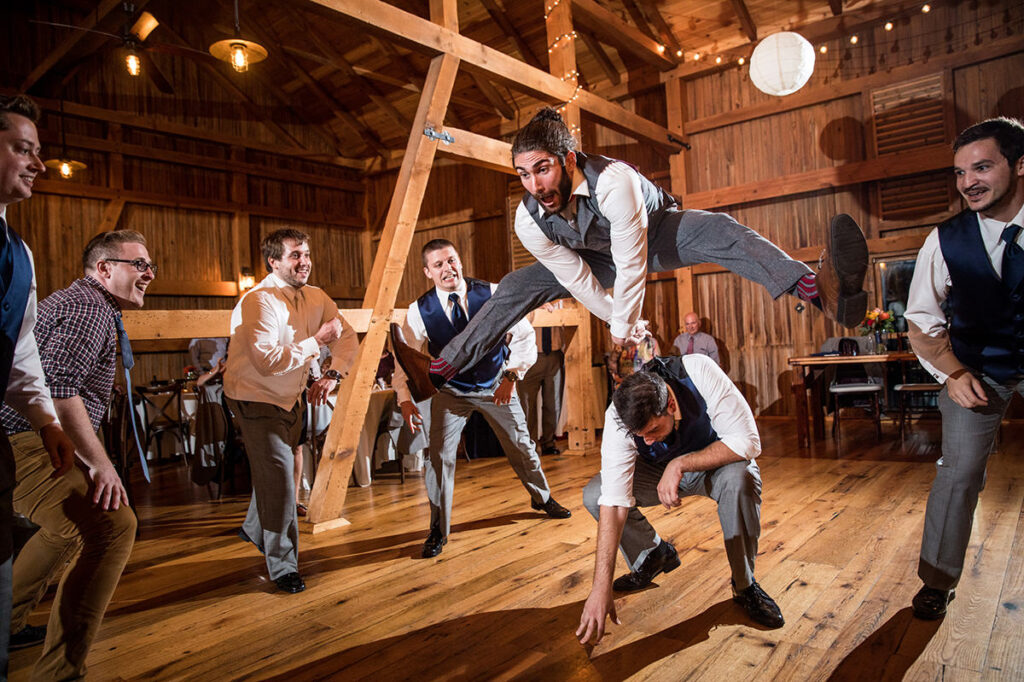 cover photo for the bridal party entrance article. This is a groomsmen jumping over the other groomsmen.