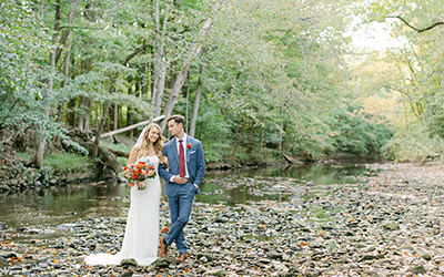 A bride and groom posing by a creek in bucks county after their wedding in pa