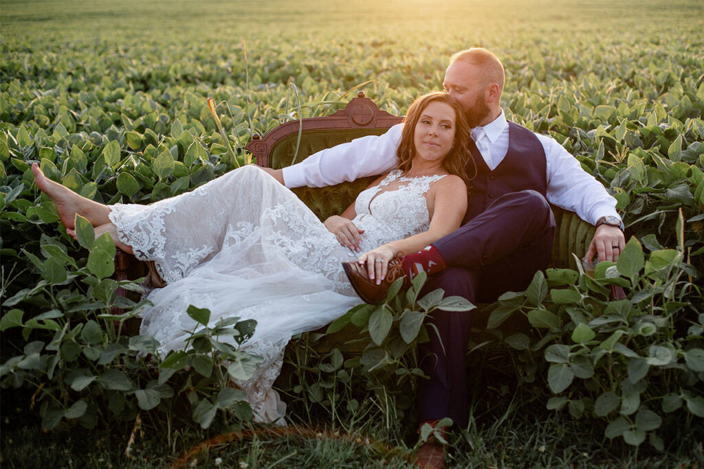 A bride and groom sitting on a couch in a field. This is the main photo for the buckscounty pa wedding photographers article.