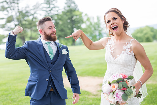A groom making a muscle while the bride looks impressed. This is for the bucks county pa wedding photographers article.