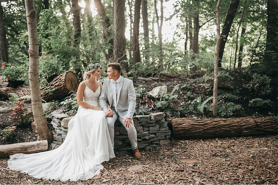 A bride and groom sitting in the woods. This is for the article called best wedding photographers in Harrisburg, PA